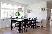 Black dining set with spoke-back chairs and white kitchen bench