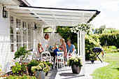 Family seated at table on roofed terrace in summery garden