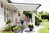 Familie am Tisch auf der überdachten Terrasse im sommerlichen Garten
