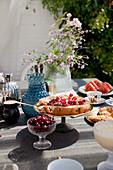 Johannisbeerkuchen auf gedecktem Gartentisch im Sommer