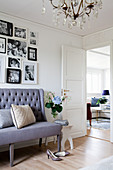 Grey sofa below gallery of family photos on wall