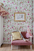 Pink couch against floral wallpaper in child's bedroom