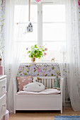 Swan-shaped cushion on white bench below window with airy curtains
