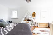 Double bed, studio lamp and cowhide rug in bedroom