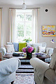 Vase of hydrangeas in living room with pale upholstered furnishings