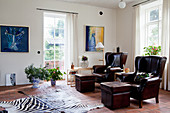 Two dark brown leather armchairs with footstools in living room