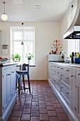 Terracotta floor tiles in bright country-house kitchen