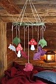 Various felt animals and toadstools hanging from hand-crafted mobile in cabin-style interior