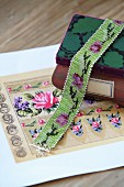 Glass-bead choker draped over wooden box and floral beading pattern