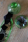 Glass-bead jewellery in green glass pot and decorated black ribbons in glass dish