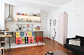 Küchenzeile und buntem Vorhang, Klassikerhocker und Retroschrank in offenem Wohnbereich
