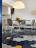 Round designer table and delicate chairs on hexagonal floor tiles