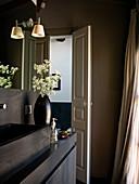 Open panelled door in bathroom with black sink