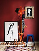 Framed picture in hall next to orange coat stand