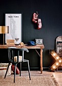 Rustic desk with brass table lamp, New York map, radio, coffee pot and hat against black wall with boxing gloves