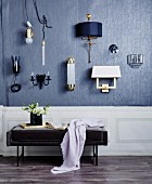 Various lights on gray wall, in front of upholstered bench with flower, book and plaid