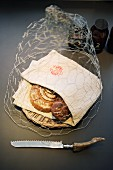 Chicken-wire cover over bread basket and linen napkin
