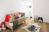 Wooden bed and fur rug in rustic child's bedroom