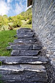 Steps leading up stone wall of stone house in the mountains