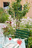 Set garden table in blooming summer garden
