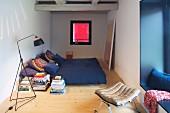 Schmales Schlafzimmer mit blauer Nische und Leseleuchte