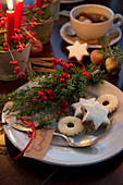 Plate of Christmas biscuits with name tag and posy of holly berries and juniper sprigs