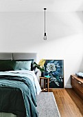 Bedroom with double bed, pendant lamp above bedside table and picture with flower motif