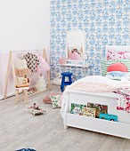 White bed with bookcase in front of blue and white pattern wallpaper and clothes rack with ballet clothes in the girls' room