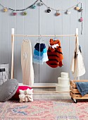 Wooden clothes rack with children's costumes in front of gray wooden paneling and pompom chain