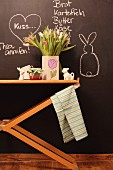 Vase of tulips and Easter ornaments on wooden table against chalkboard wall with chalk messages