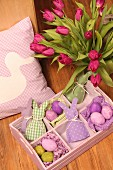 Vase of tulips and pastel Easter ornaments in wooden tray