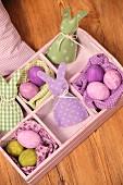 Gefärbte Ostereier und selbstgenähte Eierwärmer in einem Holzkästchen