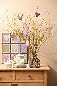Easter arrangement, coffee service and framed fabric hearts on top of chest of drawers,