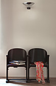Two old, black cinema seats against white wall