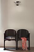 Zwei dunkle alte Kinostühle vor weißer Wand