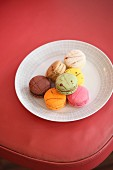 Plate of colourful macarons on red chair