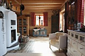 Masonry wood-burning stove, elegant armchair, chest of drawers and farmhouse trunk in open-plan interior of wooden cabin