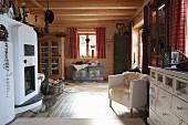 Gemauerter Kamin, eleganter Sessel neben Kommode, im Hintergrund Geschirrschrank und Bauerntruhe in offenem Wohnbereich einer Holzhütte