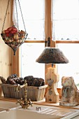 Rustic ornaments and table lamp on windowsill behind sink with vintage taps