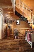 Rustikaler Treppenraum mit Holzofen und Stehleuchte in einer Almhütte