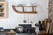 Kitchen utensils hung from old wooden sledge mounted on wall in kitchen