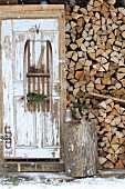 Axe and pine branches on old wooden sledge mounted on rustic wooden door and used as shelves