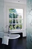 Bad mit Sprossenfenster und freistehender Badewanne auf schwarzem Fliesenboden