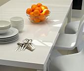 Glasschale mit Orangen, Geschirr und Besteck auf weißem Tisch