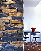 View past stone wall to bar stools around table