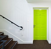 Neon-green panelled door in white stairwell with brown carpet