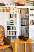 Comfortable wicker armchair, yellow side table, bookcase and kitchen area