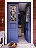 Offene, violette Eingangstür mit traditionellem Flair