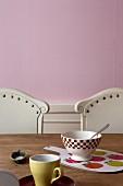 Schälchen und Schneidebrett auf Holztisch vor rosa Wand