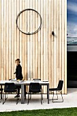 Langer Esstisch mit Stühlen vor Holzwand auf Terrasse, Frau im Hintergrund